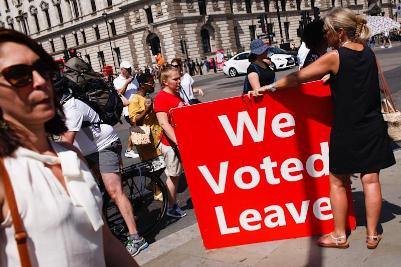 A pro-Brexit activist holds a 'We Voted Leave' board outside the Houses of Parliament in London, England, on July 24, 2019. Today sees the start of the premiership of leading Brexit advocate Boris Johnson, after Theresa May stood down as prime minister over her failure, on three occasions, to get her EU withdrawal bill through Parliament. Johnson, a deeply divisive figure lionised by his supporters as a true champion of Brexit, derided by his critics as lacking seriousness and integrity, beat his Conservative Party leadership rival Jeremy Hunt in a ballot of Tory party members by a margin of two to one. (Photo by David Cliff/NurPhoto via Getty Images)