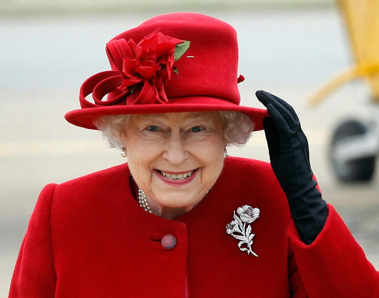 Britain's Queen Elizabeth II holds on to her hat in high winds as she arrives for a visit to RAF Valley in Anglesey, Wales on April 1, 2011. Britain's Queen Elizabeth II and Prince Philip, The Duke of Edinburgh today visited RAF Valley in Anglesey in high and were given a personal tour of an RAF search and rescue helicopter by Prince William. AFP PHOTO / Christopher Furlong /WPA POOL (Photo by Christopher Furlong / POOL / AFP) (Photo by CHRISTOPHER FURLONG/POOL/AFP via Getty Images)