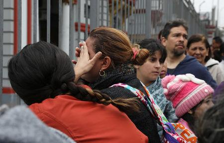 Venezuelan migrants wait outside their embassy to register for a flight to return to their country, in Lima