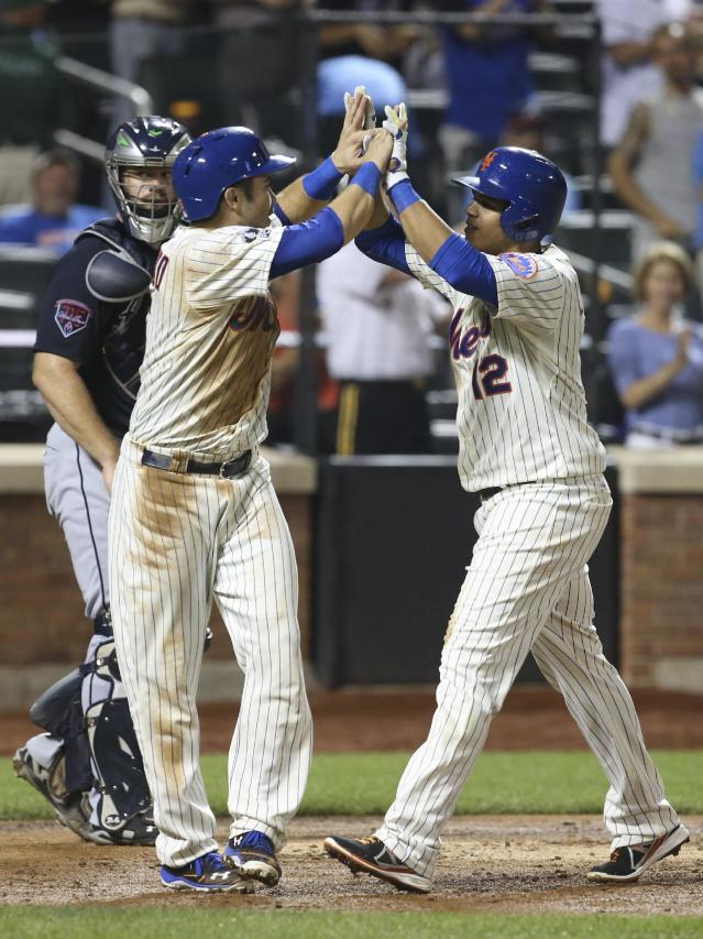 New York Mets Juan Lagares (12) celebrates alongside Travis d'Arnaud after hitting a two-run home run in the fourth inning of a baseball game against the Atlanta Braves on Tuesday, Aug. 26, 2014, in New York. (AP Photo/John Minchillo)