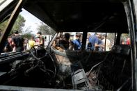 People inspect the site of a car bomb attack in Sadr City district of Baghdad