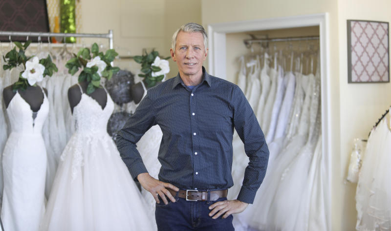 """David Gaffke, owner of the bridal salon Complete Bridal, poses in his shop in East Dundee, Illinois, on Feb. 28, 2020. He is heavily reliant on China for manufacturing. """"It's frustrating when it comes to having to tell a bride that we're not able to fulfill your needs,"""" he said. """"This is the most important dress they're going to wear."""" (AP Photo/Teresa Crawford)"""