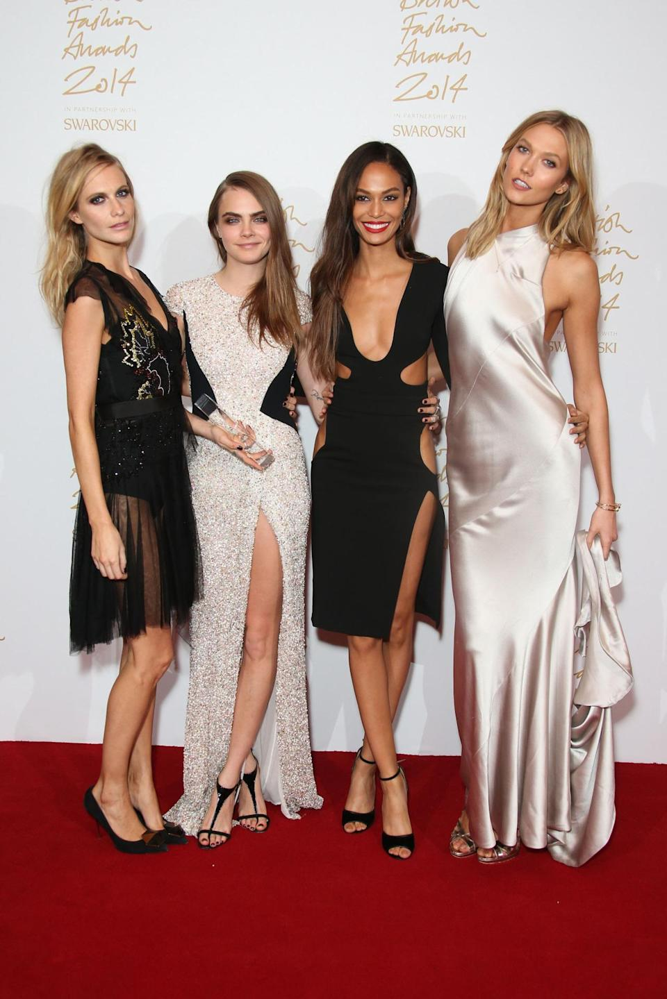 """Cara Delevingne won model of the year, wearing a ground-sweeping dress with a major thigh slit — she even revealed that she feared flashing her private parts to the paparazzi it was so high. The two-time champ was presented the award by a very special trio — her sister, Poppy Delevingne in Topshop, and friends Joan Smalls and Karlie Kloss — and her work this year proves that not only is she the queen of the British fashion scene, but the world's as well. When asked to name the instant in 2014 that stands out the most, she said: """"How dare you make me pick one moment!"""" Asked how proud she is to be British, the sexy Brit responded that she's """"ever longingly"""" and """"unconditionally"""" proud, and that's one of the reasons why she got the tattoo """"Made in England"""" on the bottom of her foot."""