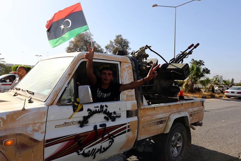 An Islamist fighter from the Fajr Libya (Libyan Dawn) coalition flashes the V sign for victory at the entrance of Tripoli international airport on August 24, 2014 (AFP Photo/Mahmud Turkia)