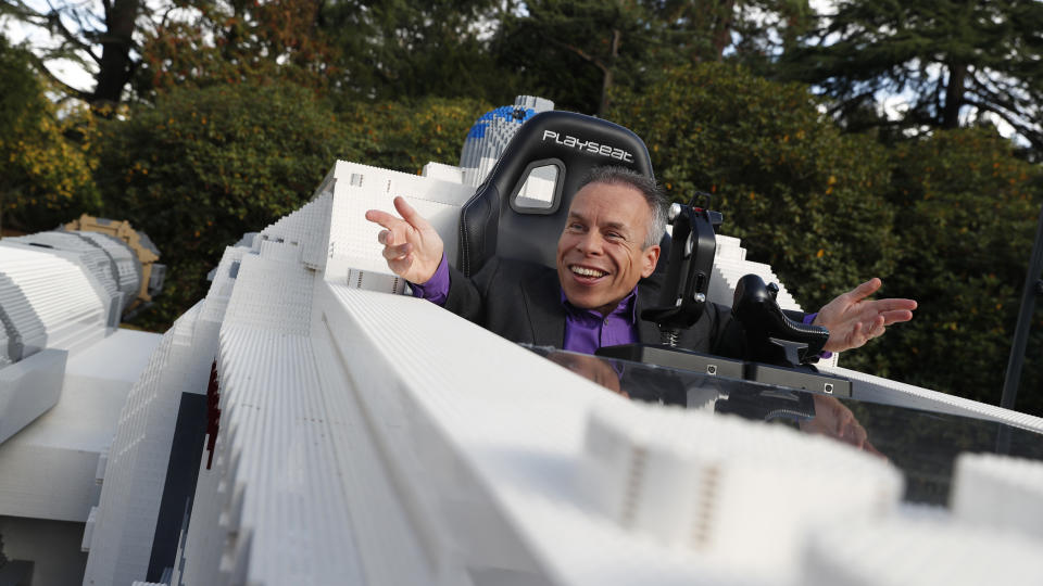 Star Wars actor Warwick Davis poses in the world's largest Lego model of a X Wing fighter at Pinewood studios outside London, Thursday, Sept. 26, 2019. Star Wars talent came together for a global livestream event for the promotion of Triple Force Friday Oct. 4, when new products inspired by the Star Wars franchise are launched worldwide. (AP Photo/Alastair Grant)