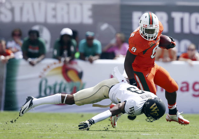 Wake Forest's Kevin Johnson (9) is unable to tackle Miami's Duke Johnson (8) during the first half of an NCAA college football game in Miami Gardens, Fla., Saturday, Oct. 26, 2013. (AP Photo/J Pat Carter)