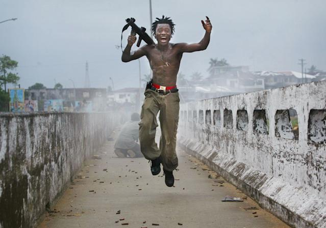 Joseph Duo, a Liberian militia commander loyal to the government exults after firing a rocket-propelled grenade at rebel forces, July 20, 2003, in Monrovia, Liberia. (Photo: Chris Hondros/Getty Images)