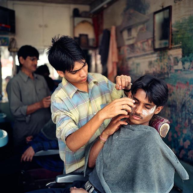 <p>A young Indian man has a close shave in a barbershop in New Delhi, India. </p>