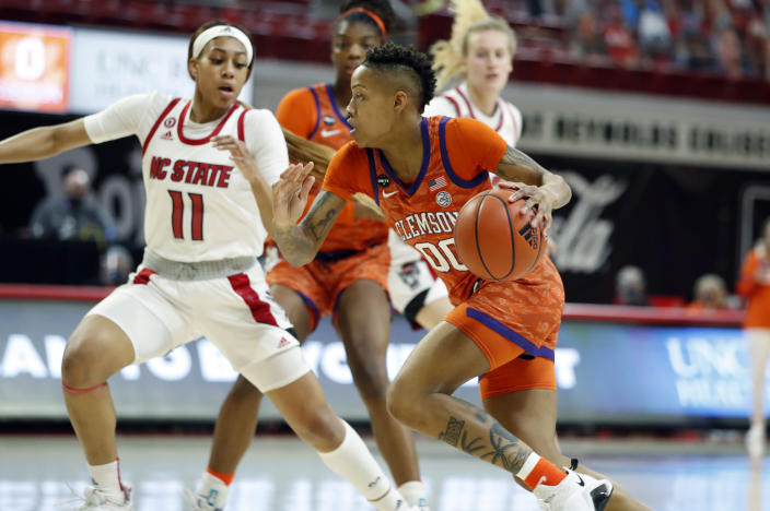 Clemson's Delicia Washington (00) drives around North Carolina State's Jakia Brown-Turner (11) during the first half of an NCAA college basketball game at Reynolds Coliseum in Raleigh, N.C., Thursday, Feb. 11, 2021. (Ethan Hyman/The News & Observer via AP)