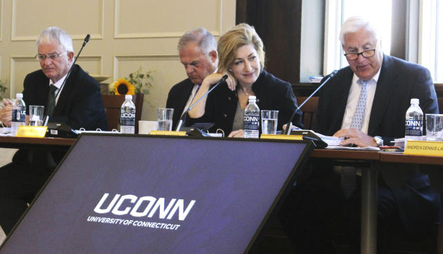 University of Connecticut Board of Trustees members, from left, Denis Nayden, Andy Bessette, UConn President Susan Herbst, and interim board chairman Tom Ritter, attend a public board meeting, Wednesday, June 26, 2019, on the school's campus in Storrs, Conn. The board is expected to accept an invitation to move most of the school's athletic teams from the American Athletic Conference to the Big East. (AP Photo/Pat Eaton-Robb)