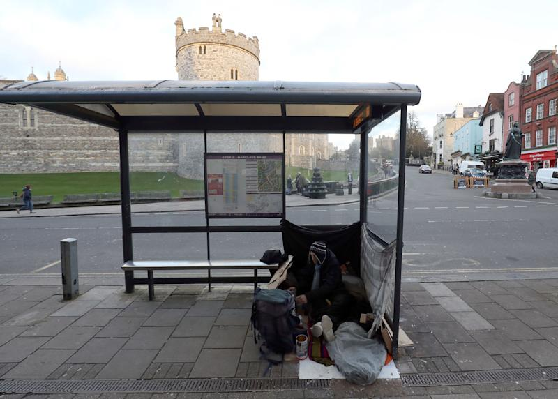 A rough sleeper in a bus stop outside Windsor Castle in Berkshire (Picture: PA)