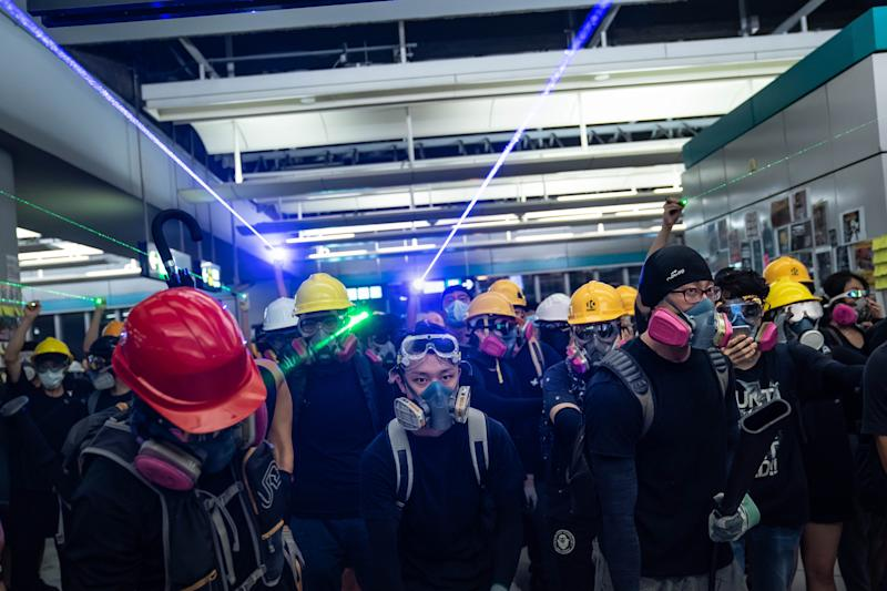 """HONG KONG, CHINA - AUGUST 21: Protestors shine laser pointers during a protest at the Yuen Long MTR station on August 21, 2019 in Hong Kong, China. Pro-democracy protesters have continued rallies on the streets of Hong Kong against a controversial extradition bill since 9 June as the city plunged into crisis after waves of demonstrations and several violent clashes. Hong Kong's Chief Executive Carrie Lam apologized for introducing the bill and declared it """"dead"""", however protesters have continued to draw large crowds with demands for Lam's resignation and completely withdraw the bill. (Photo by Billy H.C. Kwok/Getty Images)"""
