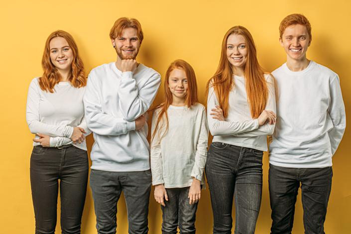 photo showing a beautiful unusual brothers and sisters with red hair, smiling at camera, feel happy together. relatives, family. people concept
