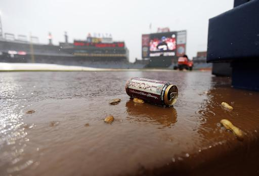 Debris washes into the Atlanta Braves dugout during a rain delay in the sixth inning of a baseball game against the Philadelphia Phillies in Atlanta, Sunday, July 20, 2014. (AP Photo/John Bazemore)