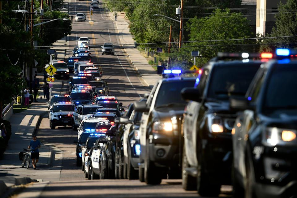 Dozens of police vehicles line up in a procession June 21 in the aftermath of a shooting in Arvada, Colo., in which a police officer was killed.