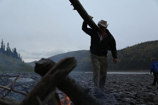 Yukon River, Alaska, USA: Marty Raney carrying a log to the campfire.