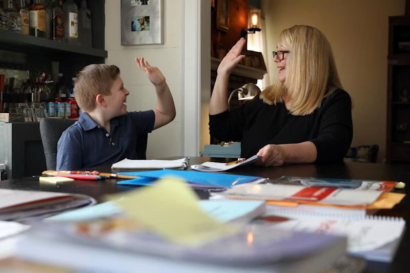 March 18, 2020; Larchmont, NY, USA; Fourth-grader Gavin Tecza hi-fives his mother, Suzanne Tecza, while working on his assignment about pioneer fun at their home in Larchmont March 18, 2020. Tecza, a library specialist at a local school, has set up a schedule to homeschool her son at home during their self-quarantine.. Mandatory Credit: Tania Savayan/The Journal News via USA TODAY NETWORK/Sipa USA