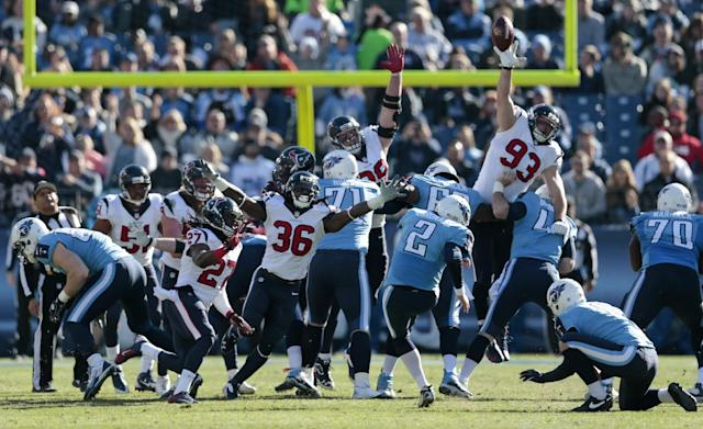 Tennessee Titans kicker Rob Bironas (2) boots a 42-yard field goal as Houston Texans defenders D.J. Swearinger (36) and Jared Crick (93) try to block the ball in the second quarter of an NFL football game on Sunday, Dec. 29, 2013, in Nashville, Tenn. (AP Photo/Wade Payne)
