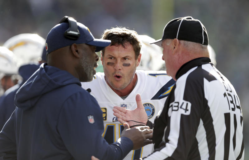 Los Angeles Chargers quarterback Philip Rivers, center, talks with head coach Anthony Lynn, left, and official Ed Camp during the first half of an NFL football game against the Seattle Seahawks, Sunday, Nov. 4, 2018, in Seattle. (AP Photo/Scott Eklund)