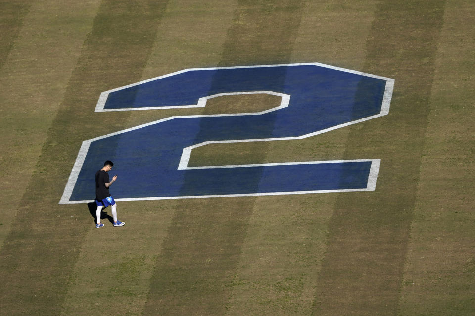 An unidentified player walks in front of a painted No. 2 in honor of Tommy Lasorda on the outfield grass at Dodger Stadium, Friday, Jan. 8, 2021, in Los Angeles. Lasorda, the fiery Hall of Fame manager who guided the Los Angeles Dodgers to two World Series titles and later became an ambassador for the sport he loved during his 71 years with the franchise, has died. He was 93. (AP Photo/Marcio Jose Sanchez)