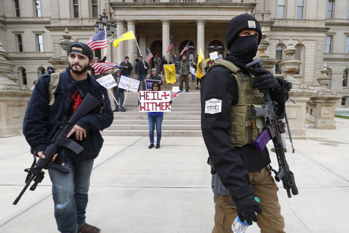 FILE - In this April 15, 2020, file photo, protesters carry rifles near the steps of the Michigan State Capitol building in Lansing, Mich. Many African Americans watching protests calling for easing restrictions meant to slow the spread of the new coronavirus see them as one more example of how their health and their rights just don't seem to matter. (AP Photo/Paul Sancya, File)