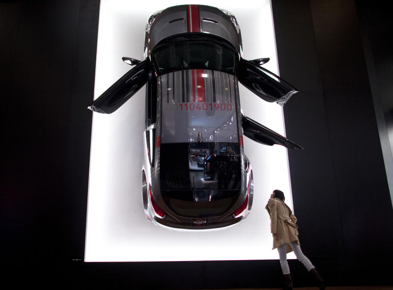 FILE - In a Tuesday, Nov. 1, 2011 file photo, a visitor checks a Hyundai Veloster mounted on the wall at an import car expo in Beijing, China. The panoramic sunroof on the Hyundai Veloster can shatter without warning, showering the driver with glass fragments. The National Highway Traffic Safety Administration is investigating the problem, although it has not recalled the cars. The probe affects about 18,000 cars from the 2012 model year, the safety agency said in documents posted on its website Friday, Oct. 5, 2012.  (AP Photo/Alexander F. Yuan, File)