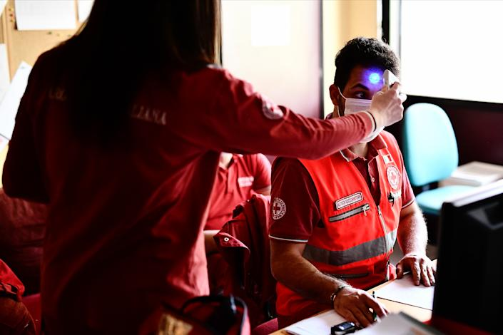 An Italian Red Cross volunteer measures the temperature of a colleague at a testing facility during the Coronavirus COVID-19 emergency on World Red Cross and Red Crescent Day on May 8, 2020 in Gavirate, Italy. (Mattia Ozbot/Soccrates Images/Getty Images)