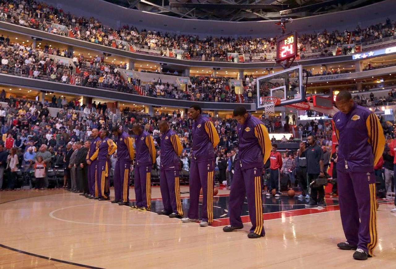 Under dimmed lights, the Los Angeles Lakers and the Washington Wizards observe a moment of silence to honor the victims of the school shootings in Connecticut, before an NBA basketball game Friday, Dec. 14, 2012 in Washington. (AP Photo/Alex Brandon)