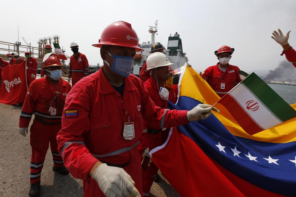 A Venezuelan oil worker holding a small Iranian flag attends a ceremony for the arrival of Iranian oil tanker Fortune at the El Palito refinery near Puerto Cabello, Venezuela, Monday, May 25, 2020. The first of five tankers loaded with gasoline sent from Iran is expected to temporarily ease Venezuela's fuel crunch while defying Trump administration sanctions targeting the two U.S. foes. (AP Photo/Ernesto Vargas)