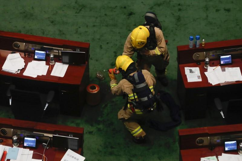 Firefighters check the chamber of the Legislative Council after pro-democracy lawmakers hurled objects during third reading on the controversial national anthem bill in Hong Kong
