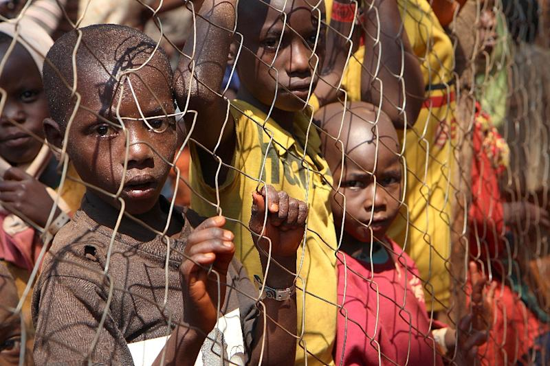 Burundian children, who fled their country, stand behind a fence as they wait to be registered as refugees at Nyarugusu camp, in north west of Tanzania, on June 11, 2015 (AFP Photo/Stephanie Aglietti)