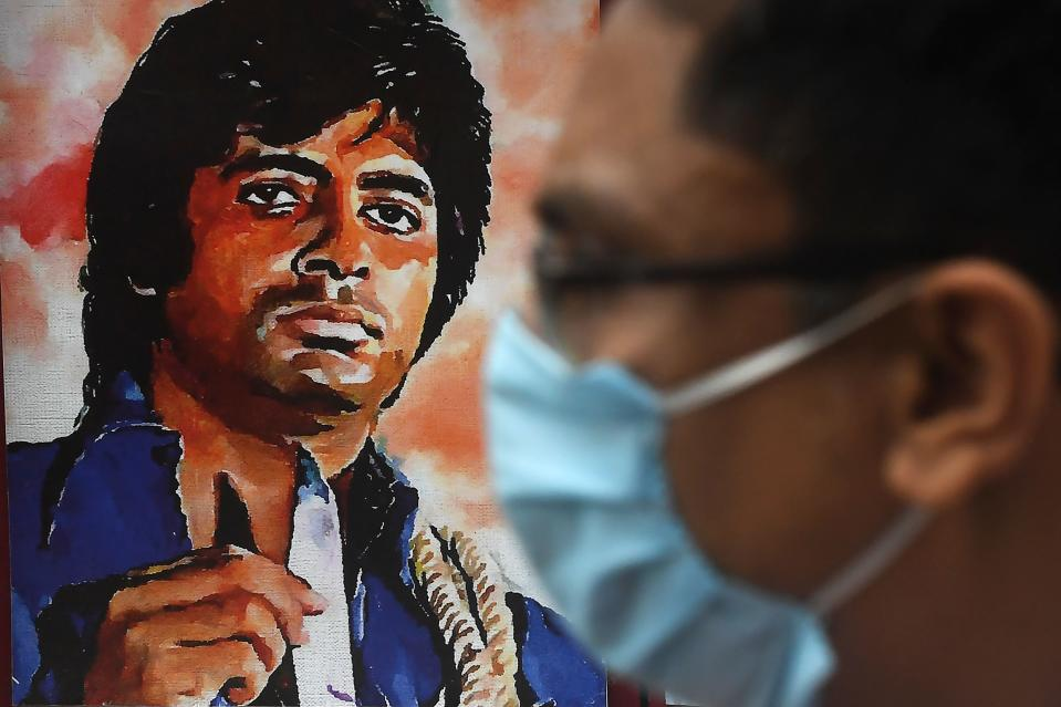 A commuter passes by a poster of Bollywood actor Amitabh Bachchan at the gate of All Bengal Amitabh Bachchan Fan Club in Kolkata on July 12, 2020. - Bollywood megastar Amitabh Bachchan, 77, tested positive for COVID-19 on July 11 and was admitted to hospital in Mumbai, with his actor son Abhishek -- who also announced he had the virus -- saying both cases were mild.(Photo by DIBYANGSHU SARKAR/AFP via Getty Images)