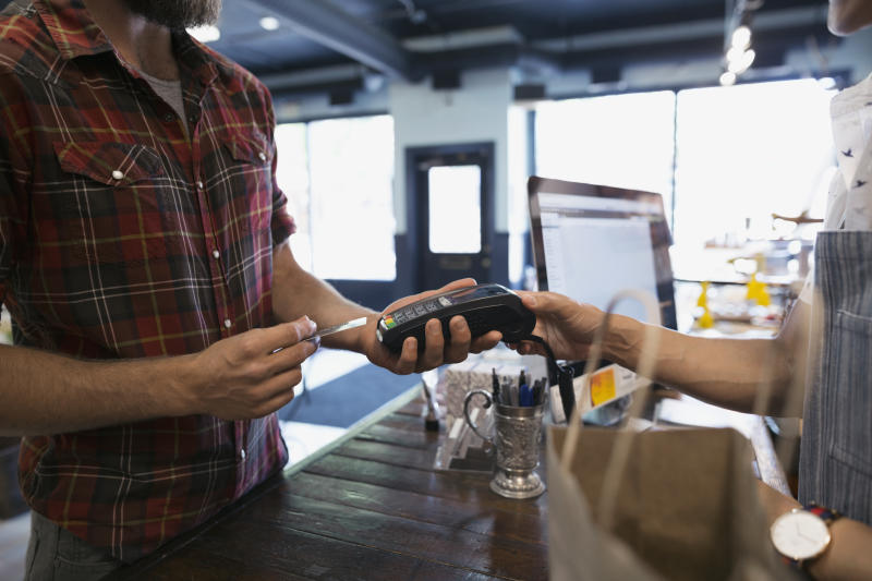 Man paying with credit card reader in shop