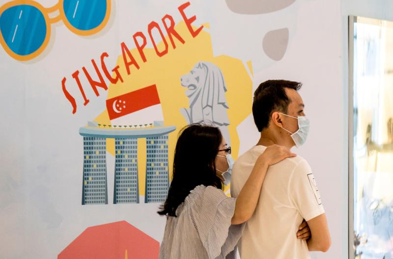 A couple, wearing protective facemasks amid fears over the spread of the COVID-19 coronavirus, walks in front of an advertisement board in Bangkok on 17 February, 2020, featuring attractions in Singapore. (PHOTO: AFP via Getty Images)