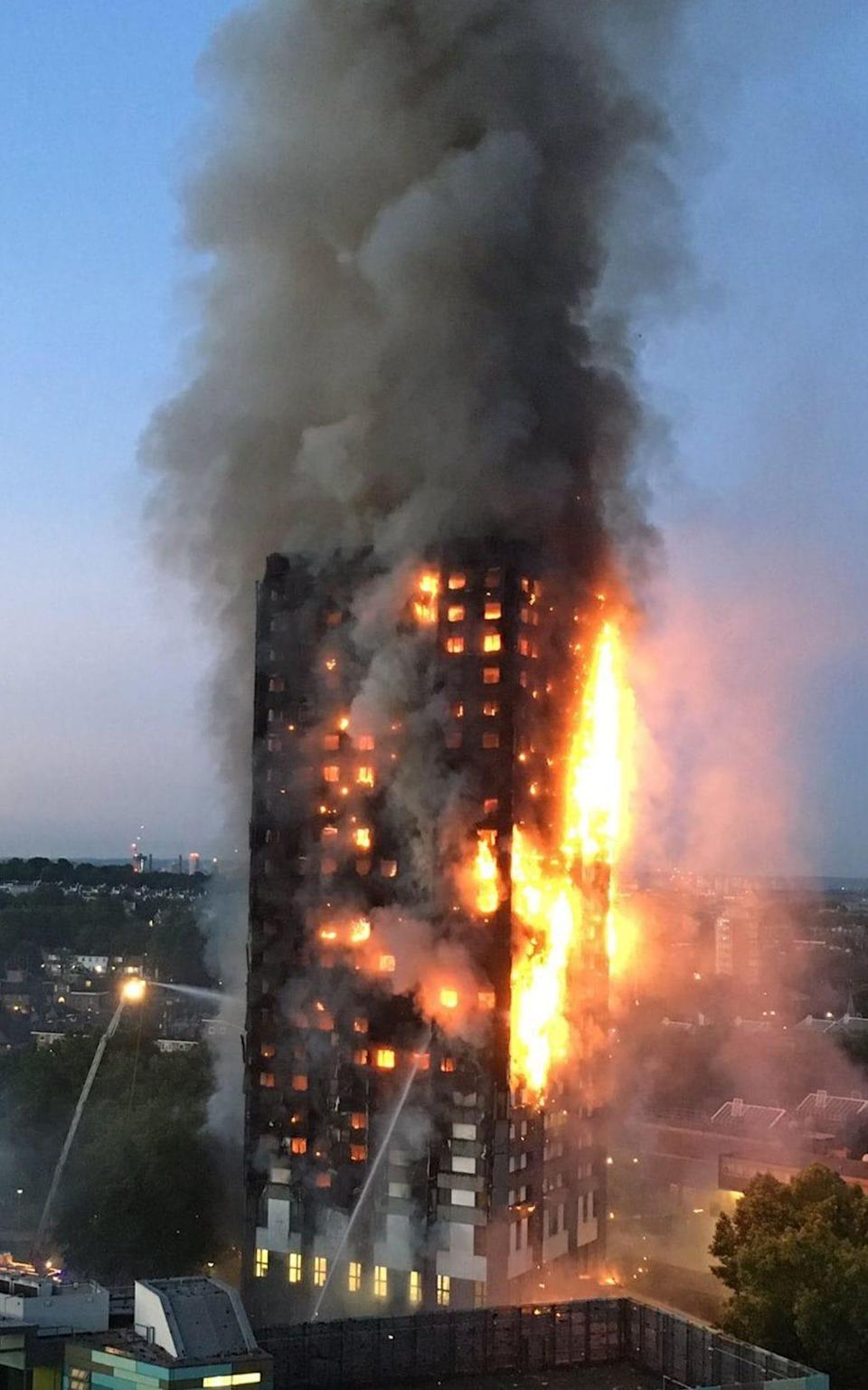 Thick smoke billows from Grenfell Tower as the fire rages in the early hours - Credit: NATALIE OXFORD/AFP