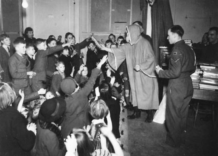 1940 photo of a soldier dressed as Santa Claus giving presents to a group of children.