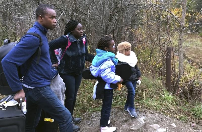 In this Nov. 4, 2019, photo, a family from Nigeria waits to illegally cross the U.S. border at Roxham Road in Champlain, N.Y., into Canada where Royal Canadian Mounted Police wait, in Saint-Bernard-de-Lacolle, Quebec. Since early 2017, when people who despaired of finding a permanent safe haven in the United States began turning to Canada for help, around 50,000 people have illegally entered Canada, many through Roxham Road in upstate New York. A case being heard in a Toronto court this week could end the use of Roxham Road. (AP Photo/Wilson Ring)