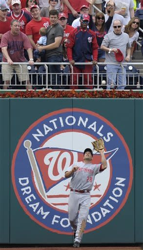 Cincinnati Reds left fielder Chris Heisley catches a fly ball hit by Washington Nationals' Rick Ankiel during the second inning of their baseball game in Washington, Saturday, April 14, 2012. (AP Photo/Susan Walsh)