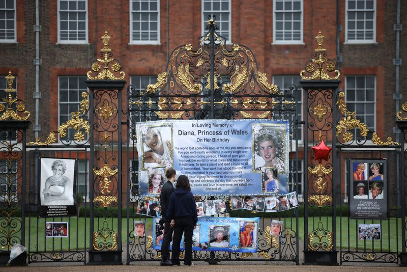 People look at tributes for Britain's Princess Diana, outside Kensington Palace in London