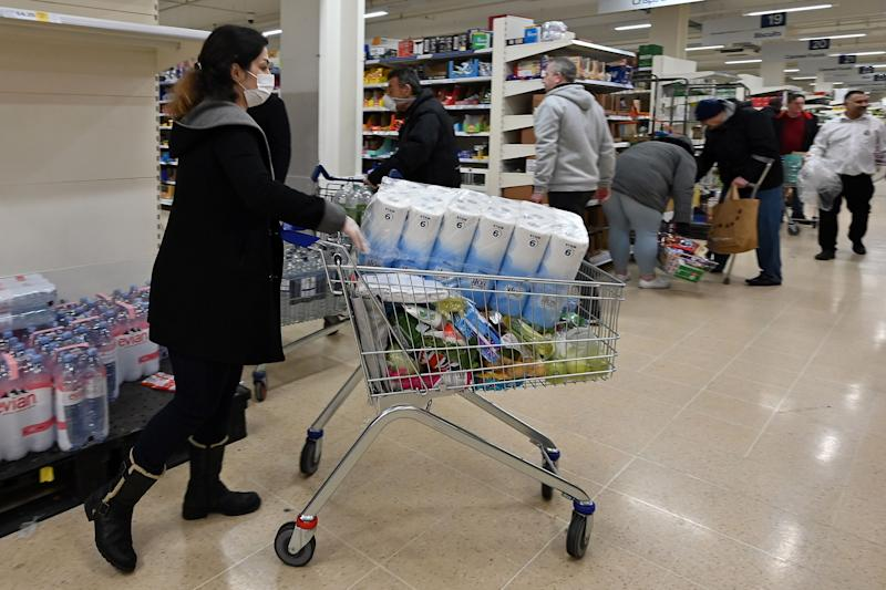 A woman wearing a mask buys toilet paper at a supermarket in London on March 14, 2020, as consumers worry about product shortages, leading to the stockpiling of household products due to the outbreak of the novel coronavirus COVID-19. - British Prime Minister Boris Johnson, who has faced criticism for his country's light touch approach to tackling the coronavirus outbreak, is preparing to review its approach and ban mass gatherings, according to government sources Saturday. (Photo by JUSTIN TALLIS / AFP) (Photo by JUSTIN TALLIS/AFP via Getty Images)