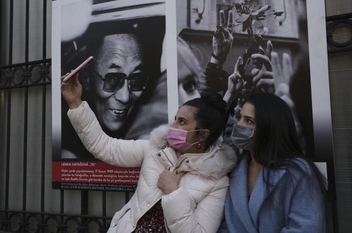 Women wearing masks to help protect against the spread of coronavirus, take a selfie, in Ankara, Turkey, Monday, Nov. 30, 2020.Turkey's President Recep Tayyip Erdogan has announced Monday the most widespread lockdown so far amid a surge in COVID-19 infections, extending curfews to weeknights and full lockdowns over weekends.(AP Photo/Burhan Ozbilici)