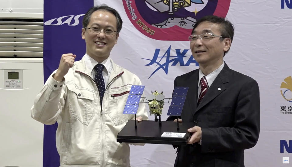 In this image made from video provided by JAXA, its project manager Yuichi Tsuda, left, and Hitoshi Kuninaka, Director General of ISAS/JAXA, pose with a Hayabusa2 model, during a press conference in Sagamihara, near Tokyo, Sunday, Dec. 6, 2020. Japanese space agency officials said Sunday they are excited about looking inside a capsule and analyzing soil samples of a distant asteroid asteroid subsurface that safely landed in the remote Australian Outback as planned. (JAXA via AP)