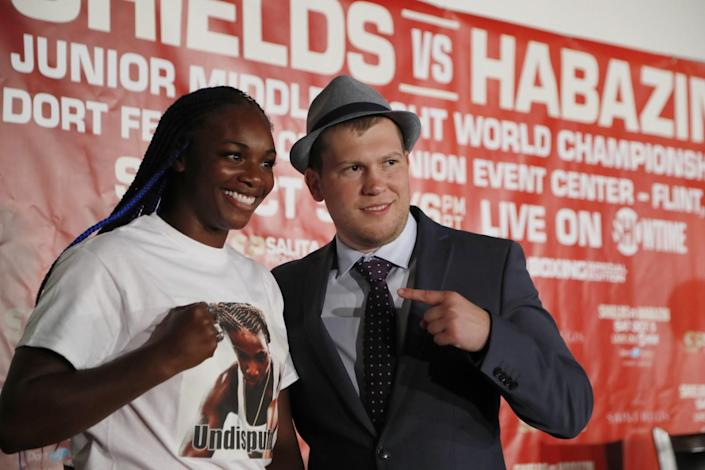Claressa Shields poses with a fist while standing next to Dmitriy Salita, who is pointing at her.