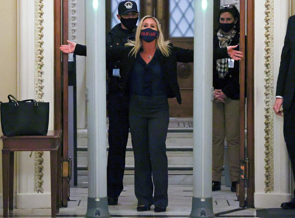 """Rep. Marjorie Taylor Greene (R-Ga), a QAnon conspiracy theorist, is searched outside the House chamber Tuesday night. Her mask says<i>molon labe</i>, a Greek phrase meaning """"come and take them"""" that the right wing uses as an anti-gun control slogan. (Photo: Jonathan Ernst / Reuters)"""