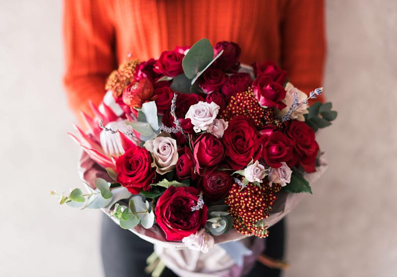 Very nice young woman in red sweater holding blossoming flower bouquet of fresh roses, carnations, eucalyptus in vivid red passionate colors on the grey wall background