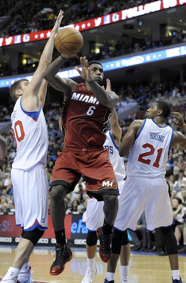 Miami Heat's LeBron James (6) passes the ball past Philadelphia 76ers' Spencer Hawes (00) and Thaddeus Young during the first half of an NBA basketball game, Wednesday, Oct. 30, 2013, in Philadelphia. (AP Photo/Michael Perez)