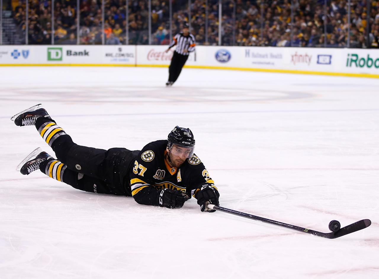 BOSTON, MA - JANUARY 04: Patrice Bergeron #37 of the Boston Bruins reaches for a loose puck in the second period against the Winnipeg Jets during the game at TD Garden on January 4, 2014 in Boston, Massachusetts. (Photo by Jared Wickerham/Getty Images)
