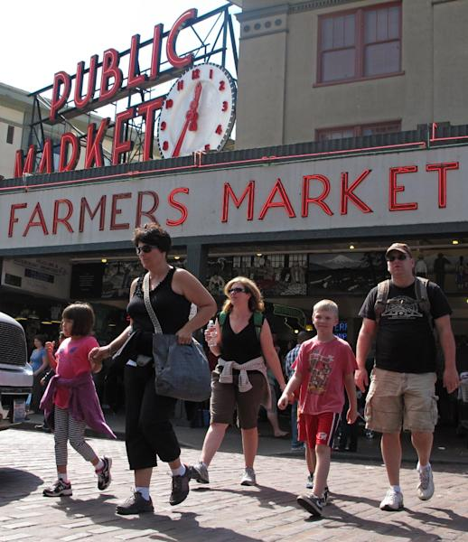 People walk in front of the iconic sign for Seattle's Pike Place Market, Friday, Aug. 31, 2012, as they enjoy a sunny day. Not too many people are complaining in typically-soggy Seattle, but the city is on a surprising run of dry weather. No rain has fallen this month at Sea-Tac Airport and the National Weather Service forecasts none on Friday, setting a record for the driest August. (AP Photo/Chris Grygiel)