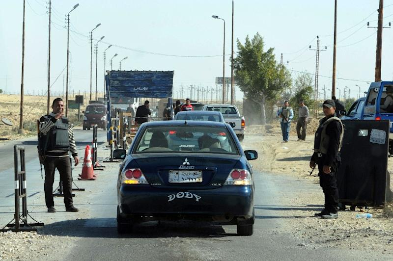 Egyptian police inspect cars at a checkpoint in North Sinai
