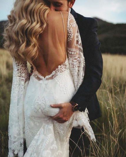 Photo of bride in field in backless gown, husband reaches over to grab her bottom, smiles into her neck.